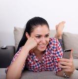 Muchacha con smartphone en el sofá Imágenes de archivo libres de regalías