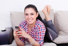 Muchacha con smartphone en el sofá Foto de archivo libre de regalías