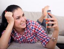 Muchacha con smartphone en el sofá Imagen de archivo libre de regalías