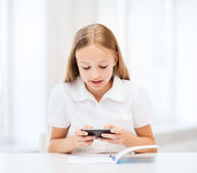Muchacha con smartphone en la escuela Imágenes de archivo libres de regalías