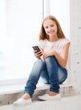 Muchacha con smartphone en la escuela Foto de archivo libre de regalías