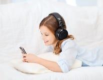 Muchacha con smartphone y los auriculares en casa Imágenes de archivo libres de regalías