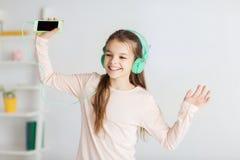 Muchacha con smartphone y los auriculares en casa Foto de archivo