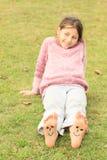 Muchacha con smiley en los dedos del pie y los lenguados Imagenes de archivo