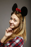 Muchacha con sonrisas de los oídos de ratón Imágenes de archivo libres de regalías