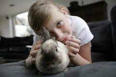 Muchacha con su conejo del animal doméstico Imagenes de archivo