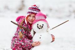 Muchacha con su diversión del invierno del muñeco de nieve Foto de archivo libre de regalías