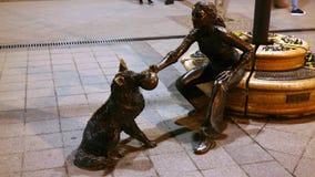 Muchacha con su estatua del perro Imagenes de archivo