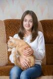 Muchacha con su gato rojo Fotos de archivo libres de regalías