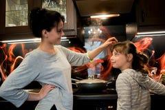 Muchacha con su madre en la cocina en la estufa Foto de archivo