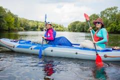 Muchacha con su madre kayaking Imagen de archivo