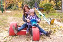 muchacha con su madre que se sienta en el children& x27; motocicleta hecha en casa de s en la yarda Fotos de archivo