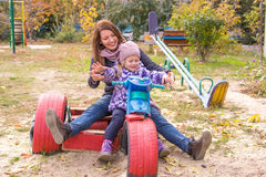 muchacha con su madre que se sienta en el children& x27; motocicleta hecha en casa de s en la yarda Imagen de archivo