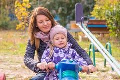 muchacha con su madre que se sienta en el children& x27; motocicleta hecha en casa de s en la yarda Foto de archivo libre de regalías