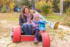 muchacha con su madre que se sienta en el children& x27; motocicleta hecha en casa de s en la yarda Foto de archivo