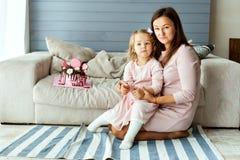 Muchacha con su madre y una torta de cumpleaños Foto de archivo