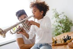 Muchacha con su padre que aprende la trompeta Fotos de archivo libres de regalías