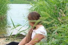 Muchacha con su pelo abajo en el río en un día de verano Imagenes de archivo