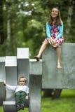 Muchacha con su pequeño hermano en el patio en parque de la ciudad Fotos de archivo libres de regalías