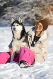 Muchacha con su perro esquimal lindo del perro en un paseo Fotografía de archivo libre de regalías