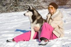 Muchacha con su perro esquimal lindo del perro en un paseo Imágenes de archivo libres de regalías