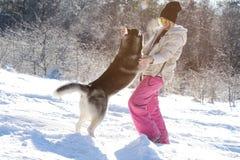 Muchacha con su perro esquimal lindo del perro en un paseo Imagenes de archivo