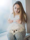 Muchacha con su perro que se sienta en la PC de la tableta del alféizar y del uso en casa Fotos de archivo libres de regalías