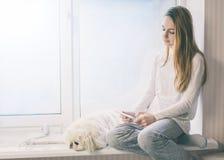 Muchacha con su perro que se sienta en la PC de la tableta del alféizar y del uso en casa Imagen de archivo