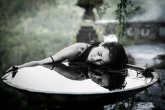 Muchacha con su reflexión en cuenco grande en el hotel abandonado místico en Bali indonesia foto de archivo