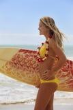 Muchacha con su tabla hawaiana en la playa Foto de archivo