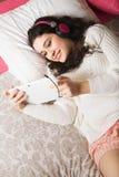 Muchacha con su tableta en cama Imágenes de archivo libres de regalías