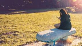 Muchacha con su teléfono en el banco Imagen de archivo libre de regalías