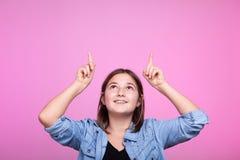 Muchacha con sus manos para arriba poiting en el aire Imagen de archivo libre de regalías