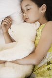 Muchacha con Teddy Bear Sleeping In Bed Imagenes de archivo