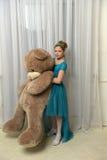Muchacha con teddybear enorme Foto de archivo