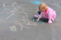 Muchacha con tiza en el asfalto Imagen de archivo