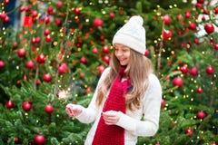 Muchacha con un árbol de navidad cercano de la bengala brillantemente Imagen de archivo libre de regalías