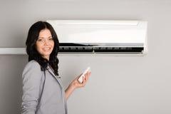 Muchacha con un acondicionador de aire teledirigido foto de archivo