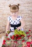 Muchacha con un apetito para comer las fresas frescas Imágenes de archivo libres de regalías