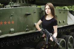 Muchacha con un arma cerca de los vehículos blindados imagen de archivo libre de regalías