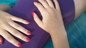 Muchacha con un bañador púrpura y clavos rojos Foto de archivo libre de regalías