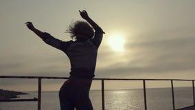 Muchacha con un baile incendiario de la figura atractiva y del pelo corto en el embarcadero cerca del mar en la puesta del sol