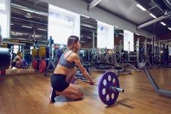 Muchacha con un barbell en el gimnasio Fotos de archivo