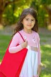 Muchacha con un bolso con las compras en parque Fotos de archivo libres de regalías