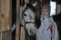 Muchacha con un caballo stabled Imagen de archivo