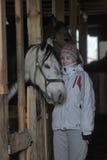 Muchacha con un caballo stabled Fotos de archivo libres de regalías