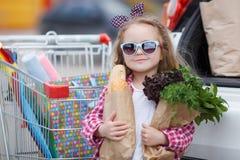 Muchacha con un carro de la compra lleno de ultramarinos cerca del coche Fotografía de archivo libre de regalías