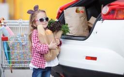 Muchacha con un carro de la compra lleno de ultramarinos cerca del coche Fotos de archivo