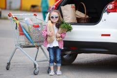 Muchacha con un carro de la compra lleno de ultramarinos cerca del coche Foto de archivo libre de regalías