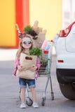 Muchacha con un carro de la compra lleno de ultramarinos cerca del coche Imagen de archivo